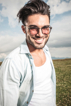 cool people: Close up picture of a happy young man posing outdoor. Stock Photo