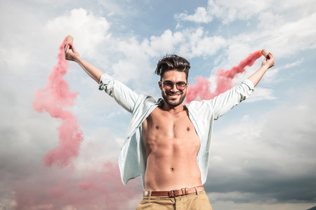 producing: Happy young casual man celebrating freedom outside, holding smoke producing tubes in both hands. Stock Photo