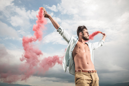 Side view of a young casual man holding in both hands smoke producing tubes. He is holding both arms up while looking away. photo