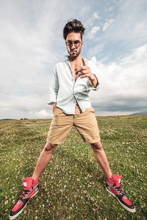 legs apart: Foto de cuerpo entero de un apuesto joven de pie con las piernas separadas, la celebraci�n de una mano en el bolsillo, mientras que se�ala en usted. Foto de archivo