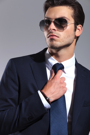 Close up picture of a young business man looking away while fixing his tie. photo