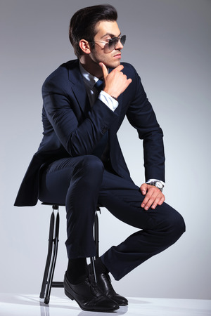 gray suit: Side view picture of a young business man sitting on a stool, thinking while holding his hand to his chin.