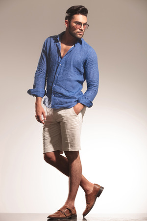 body image: Full body image of a handsome young casual man looking away from the camera while holding one hand in his pocket.