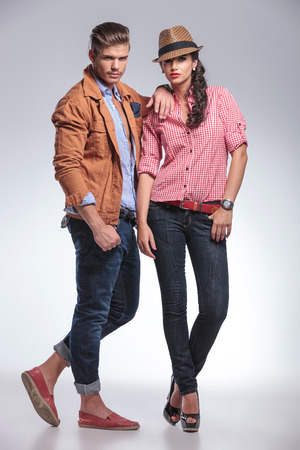 Full body picture of a young fashion couple posing on grey studio background, the man is leaning on the woman.