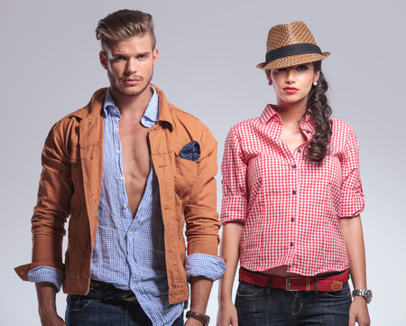 poses de modelos: Mujer hermosa joven que presenta en el estudio de fondo gris al lado de un hombre joven y guapo.