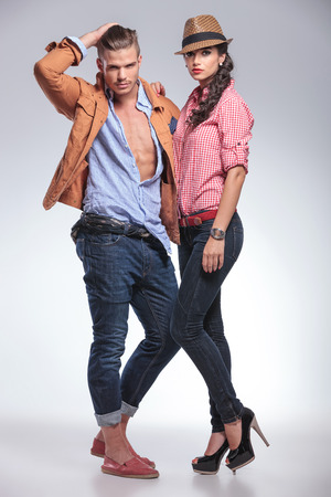 Side view of a young fashion couple posing together, the man is fixing his hair.
