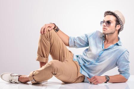 ファッション: クールなファッション男は床に横になっている、1 つの膝を持ち上げて、カメラから離れています。