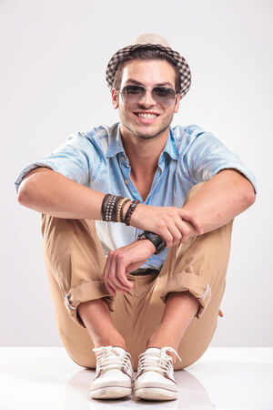knees up: Young casual man sitting on studio background with his knees up, holding his hands together, smiling.