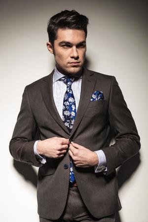 cerrando negocio: Apuesto hombre de negocios mirando a la c�mara, mientras que el cierre de su chaqueta, sobre fondo de estudio.