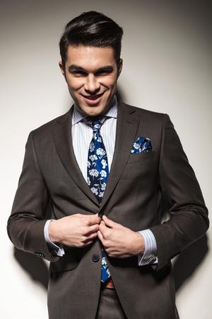 cerrando negocio: Sonriente hombre de negocios de cerrar su chaqueta mientras mira a la c�mara. Foto de archivo