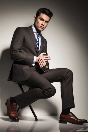 Side view picture of a young elegant business man sitting with one leg in front of the other, looking at the camera. Imagens