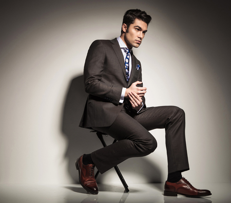 other side of: Full body picture of a young elegant business man sitting with one leg in front of the other, looking away with his hands together. Side view picture. Stock Photo