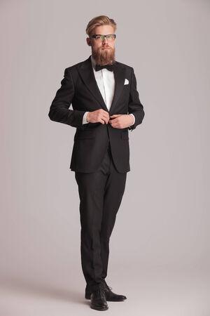 cerrando negocio: Foto de cuerpo entero de un hombre de negocios elegante que se coloca en gris backgroud estudio mientras que el cierre de su chaqueta. Foto de archivo