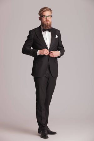 Full length picture of a elegant business man standing on grey studio backgroud while closing his jacket. photo