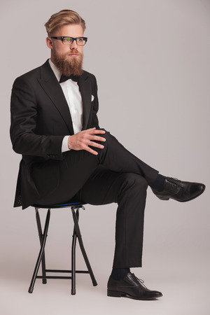 legs crossed at knee: Full body picture of a blonde business man sitting on a stool with his legs crossed, looking away from the camera. He is holding one hand in his knee