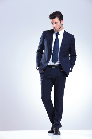 man looking down: Full length picture of a young elegant business man looking down while holding both hands in his pockets. Stock Photo
