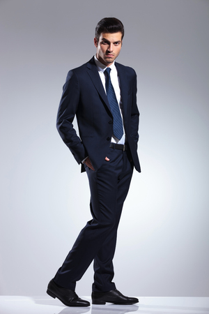 body image: Side view image of a elegant business man looking at the camera with his hands in pockets. Full body image. Stock Photo