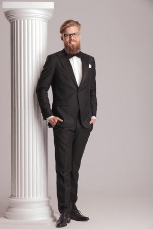 elegant business man: Quadro completo del corpo di un giovane elegante uomo d'affari in posa con le mani in tasca vicino a una colonna bianca.