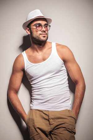 undershirt: Handsome young fashion man holding both hands in his pocket while leaning on a white wall, looking away from the camera.