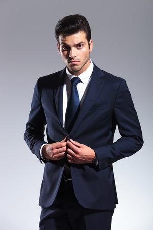 cerrando negocio: Hombre de negocios elegante mirando a la c�mara mientras se cierra la chaqueta.