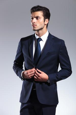 cerrando negocio: Atractivo joven hombre de negocios mirando hacia arriba mientras que el cierre de su chaqueta. Sobre fondo gris de estudio.