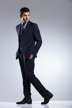 Seitenansicht Bild von einem jungen Geschäftsmann, der auf grauem Hintergrund Studio mit seinen Händen in den Taschen. Standard-Bild