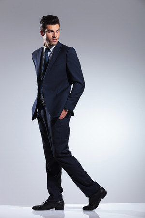 Side view picture of a young business man walking on grey studio background with his hands in pockets. 版權商用圖片