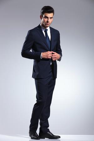 cerrando negocio: Vista lateral retrato de un apuesto hombre de negocios de cerrar su chaqueta mientras mira lejos de la c�mara.