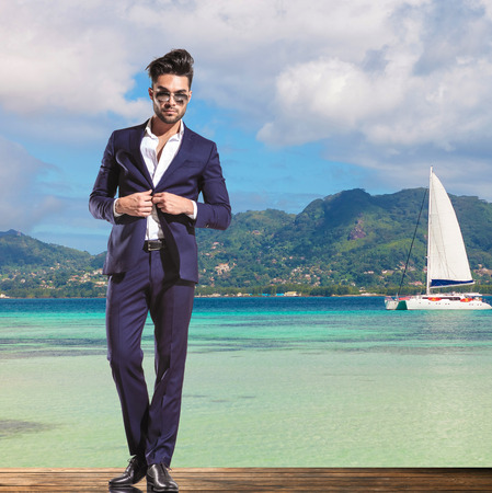 business suit: handsome young business man wearing sunglasses is unbuttoning his suit while standing on a deck on the shore of the sea, little boat sailing in the background