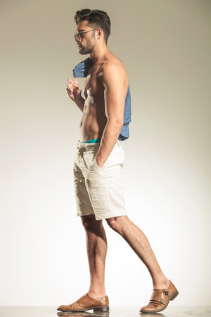 naked abs: Side view of a young sexy casual man walking on studio background with his shirt on his shoulder.