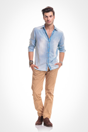 Full length picture of a young fashion man standing on studio background holding both hands in his pocket. Stock Photo