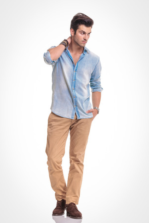 latin man: Attractive fashion man walking on studio background with one hand in his pocket while looking away from the camera.