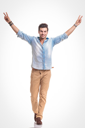 holding hands while walking: Young fashion man walking on white studio background holding both hands in the air while showing the victory sign.