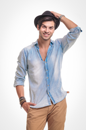 hand in pocket: Young handsome man smiling at the camera while holding one hand in his pocket while fixing his hat.