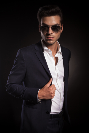 unbuttoned: Portrait of a elegant business man posing on black studio background, fixing his jacket while looking at the camera.