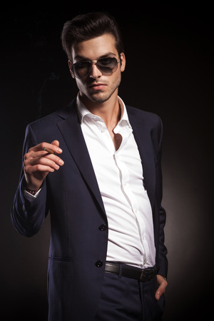 man smoking: Portrait of a young elegant business man looking at the camera while smoking a cigarette.