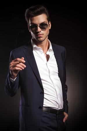 hombre fumando puro: Retrato de un joven elegante hombre de negocios mirando a la cámara mientras se fuma un cigarrillo. Foto de archivo