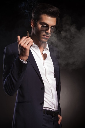 man looking down: Handsome elegant business man looking down while holding a cigarette in his right hand. Stock Photo