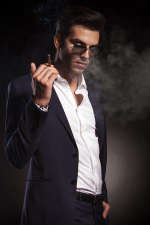 cigarro: Hombre de negocios elegante mirando hacia abajo mientras sostiene un cigarrillo en su mano derecha. Foto de archivo
