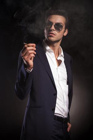 elegant business man: Uomo elegante di affari guardando mentre godendo una sigaretta.