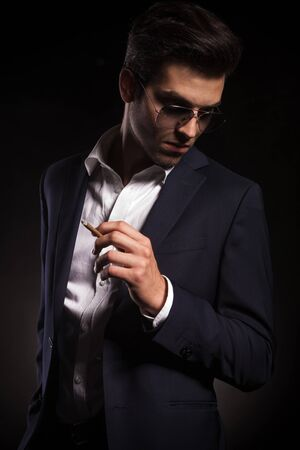 man looking down: Elegant business man looking down while holding a cigarette in his left hand. Stock Photo