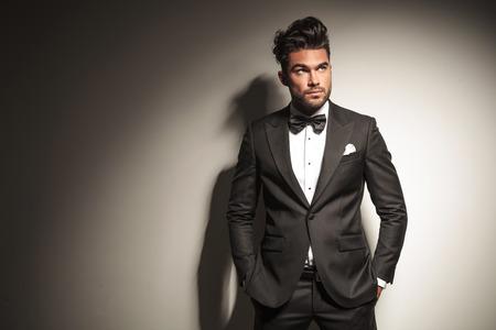 stile: Immagine di un giovane uomo d'affari guardando mentre si tiene le mani in tasca.