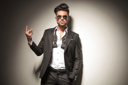 Handsome young business man wearing sunglasses holding one finger up. Stock Photo