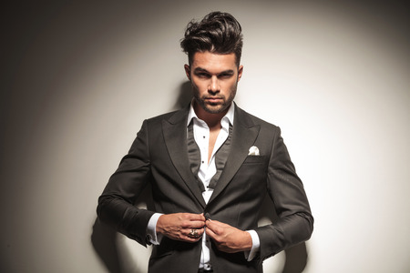 elegant business man: Handsome elegante uomo d'affari guardando la telecamera, mentre sbottona la giacca.