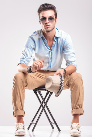 casual fashion: Casual fashion man sitting on a stool, holding his hat in his left hand while looking at the camera. Stock Photo
