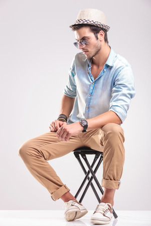 man looking down: Side view of a casual fashion man sitting on a stool while looking down. Stock Photo