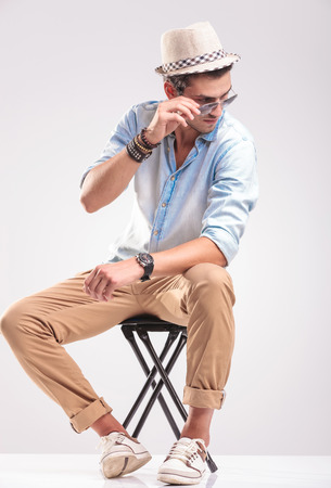 taking off: Full body picture of a young casual man sitting on a stool while taking off his sunglasses, looking down.