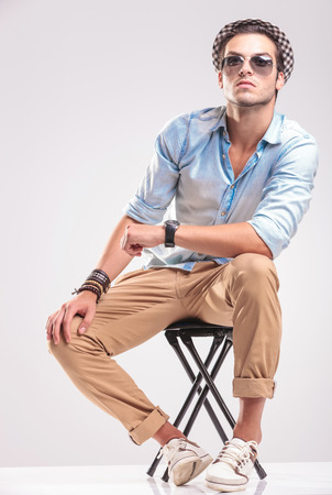 siting: Cute fashion man sitting on a stool while looking up, rsting his hands on his knee. Stock Photo