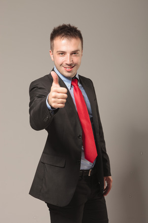 succes: Happy young business man celebrating a succes by showing the thumbs up gesture.