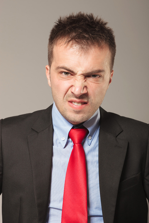 disapproving: Young business man making a disapproving face, on studio background.